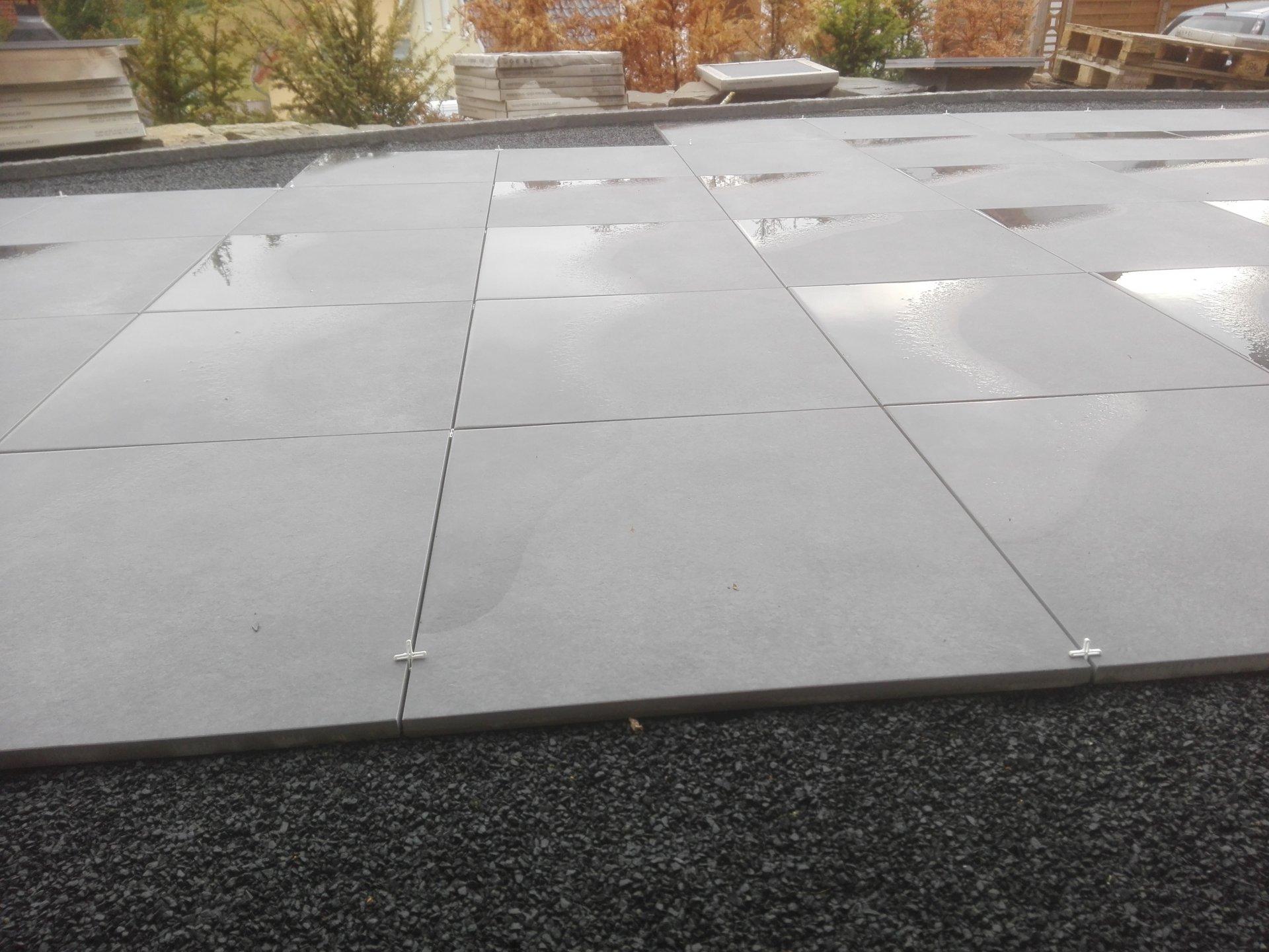 Wasser bleibt auf den Terrassenplatten stehen.